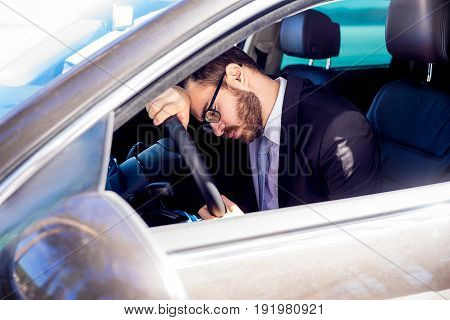 Portrait of a tired man sitting in his car