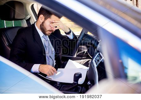 Man is tired and sitting in his car