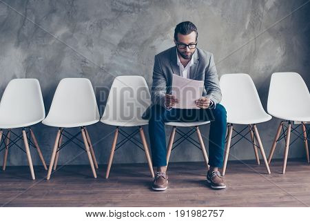 Serious Bearded Young Man In Glasses And Formal Wear Is Preparing For A Meeting, Sitting In The Hall