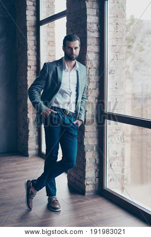 Full Length Of Young Bearded Man, Who Is Standing Near The Window With Crossed Legs And Looking In C