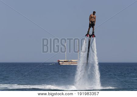 CAMYUVA KEMER TURKEY - JULY 16 2015: Unidentified Turkish man hovered above the water. Extreme water sports are increasingly popular on the beaches of Turkey