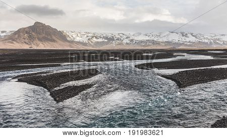 Rocky Riverbed And Stream With Mountains On Background In Iceland