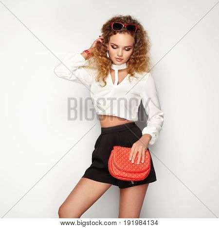 Blonde woman in summer blouse and shorts. Girl posing on white background. Red handbag. Stylish curly hairstyle. Glamour lady in stylish sunglasses