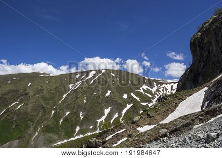 Mountain landscape, beautiful view of picturesque hillsides, panorama of the mountain gorge, white clouds in the sky, the wild nature and mountains of the North Caucasus