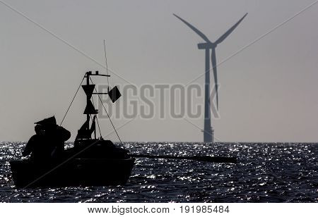 Sustainable resources. Small fishing boat silhouetted infront of a solitary wind turbine from offshore wind farm. Moonlit sea. Peaceful green planet image.