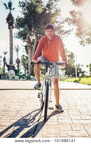 Portrait of handsome guy riding bicycle in the park.
