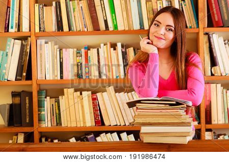 Education school concept. Intelligent female student fashion long hair girl in college library with stack books making research