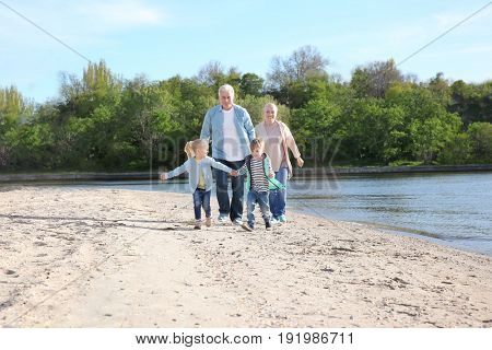 Happy grandparents playing with little children on river bank