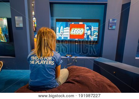 Cologne, Germany, August 13, 2014: The girl in the playstation players shirt playing lego game. Gamescom is a trade fair for video games held annually at the Koelnmesse in Cologne.