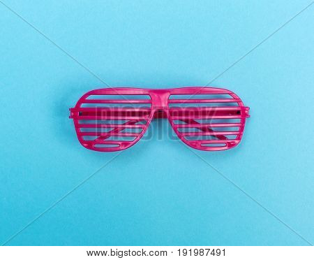 A pair of party shutter shades on a bright blue background