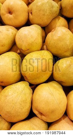 Group of stacked fresh yellow fruit pears