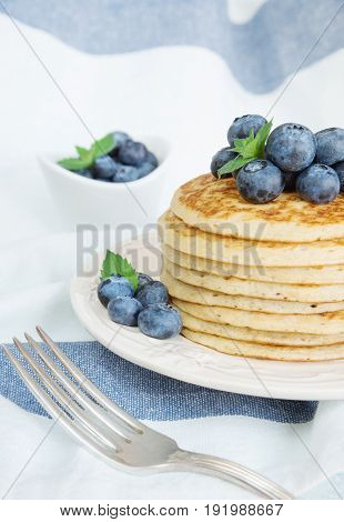 Stack of pancakes decorated with ripe berries of blueberries on the background of blue-white napkin