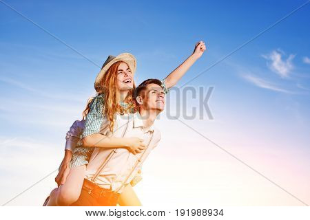 Young Man Piggybacking His Happy Girlfriend With Raised Hand. Cheerful Lovers Dreaming