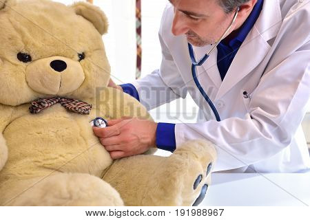 Pediatrician Doctor Behind Table Auscultating Teddy
