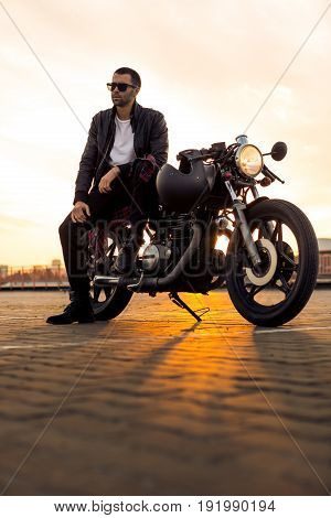 Handsome rider guy with beard and mustache in black leather biker jacket and sunglasses sit on classic style cafe racer motorcycle. Bike custom made in vintage garage. Brutal fun urban lifestyle.