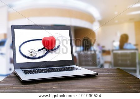 Laptop notebook computer with red heart and stethoscope on white background on wooden table with blur hospital background heart health care and medical technology concept selective focus sunlight
