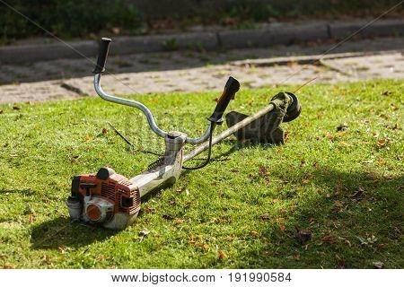 Brushcutter mower lying on green grass. Seasonal garden cleaning moder objects concept.