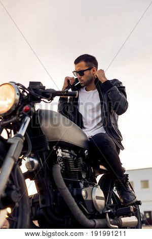 Handsome young rider guy with beard and mustache in black fashion sunglasses smoking cigaret and correct biker jacket sit on classic style cafe racer motorbike at sunset. Brutal fun urban lifestyle.
