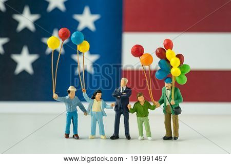 miniature figure happy american family holding balloon with United State national flag in the background as celebrating the Independence day.