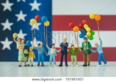 miniature people happy american family holding balloon with United State national flag in the background as celebrating the Independence day.