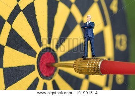 Business goal or target concept with a miniature businessman standing on the red dart in the center of dartboard.