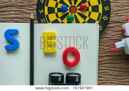SEO search engine optimization concept with pencil alphabets SEO on paper note dartboard robot and binoculars.