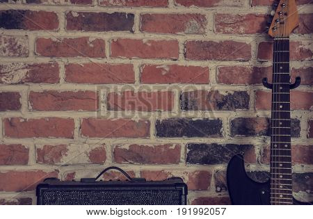 amplifier and guitar against the red brick wall in the background