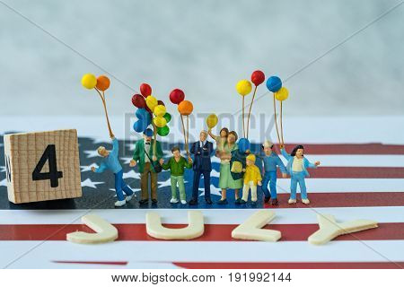 Independence day celebration with miniature happy american family holding balloons and wooden block and alphabet as 4 July on United State national flag background.