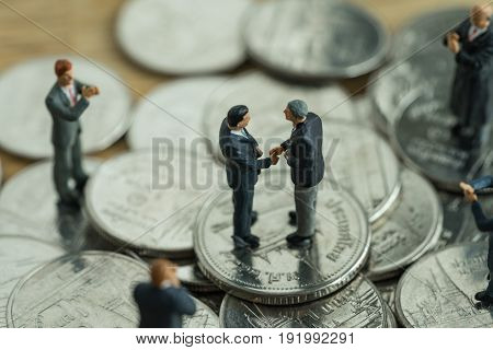 financial business agreement concept with miniature small figure businessmen handshaking and others clapping on stack of coin.