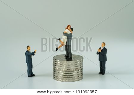 Miniature people with couple standing on top stack of coins and other clapping with white background as success love life concept.