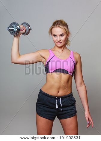 Strong woman lifting dumbbells weights. Fit girl exercising gaining building muscles. Fitness and bodybuilding.