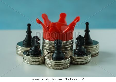 Miniature red crown king on stack of coins and chess symbol as financial business growth success concept.