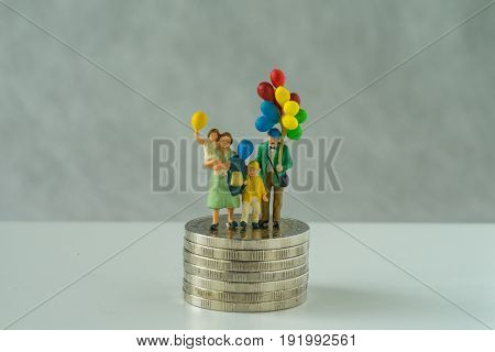 Miniature people family holding balloon standing on stack of coins as financial business or happy retirement concept.