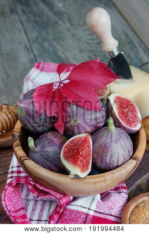 Ripe figs in a wooden bowl cheese cane sugar honey and a checkered napkin on old cutting board as well as red autumn leaves lie on the old wooden table. Vertical photo