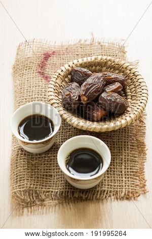 Sweet dates in a straw basket served with traditional arabic black coffee.