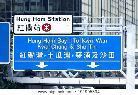 Large road signs in English and Chinese on Hong Kong highway show directions to different parts of the city