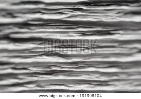 White texture of embossed paper. Macro. Shallow depth of field. Abstract background with deep grooves in the texture of corrugated paper. Pattern of horizontal grooves