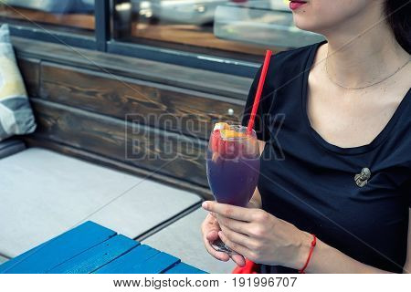 Close up young beautiful woman holding glass with dark cocktail with grapefruit in outdoors reastaurant