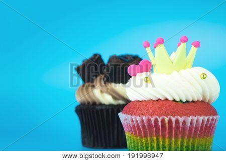 King Cupcake Rainbow muffin with Chocolate brownie cupcake on blue background