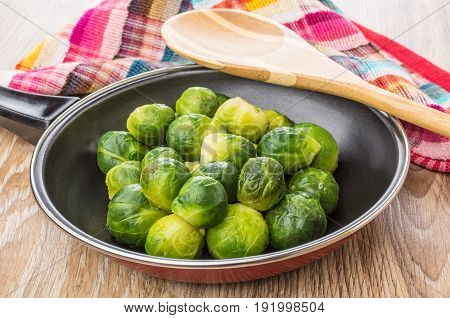 Frying Pan With Brussels Sprouts, Wooden Spoon And Napkin
