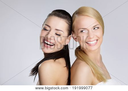 Two Pretty Women Leaning On Each Other Back Laughing