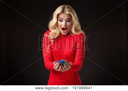 Young beautiful emotional woman with chips in hands on a black background in the studio. Portrait of a beautiful blonde in a red dress. Poker
