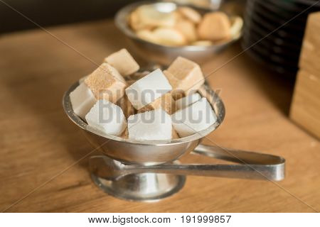 Close up white and dark cane sugar cubes in metal bowl