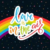 Love is in the air. Words on rainbow parade flag at dark sky with stars. Gay pride saying for stickers, t-shirts and posters poster