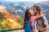 Couple in love kissing on nature travel hiking in Hawaii mountains. Young hikers people happy together. Interracial backpacking lovers kiss portrait on vacation hike. poster