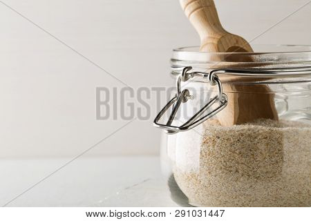 Heap Of Psyllium Husk Also Called Isabgol In Glass Jar With Wooden Scoop On White Table Background.