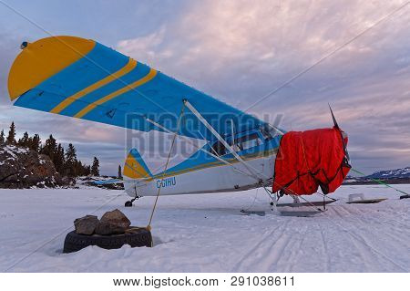 Whitehorse, Yukon, Canada, March 10, 2019 : Ski Airplane At Dawn On The Frozen Laberge Lake, On The