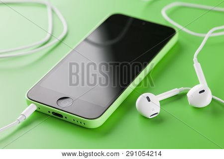 Tambov, Russian Federation - October 16, 2013 Apple Iphone 5c Green Color With New Apple Earpods On