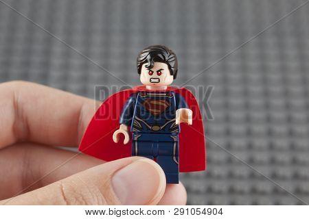 Tambov, Russian Federation - July 26, 2014 Lego Superman Minifigure In Human Hand On Lego Gray Basep