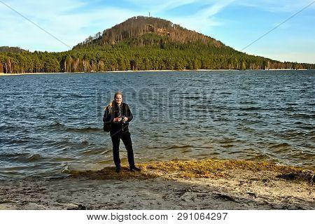 Stare Splavy, Czech Republic - March 06, 2019: Photographer Jiri Igaz Stand By Machovo Jezero Lake